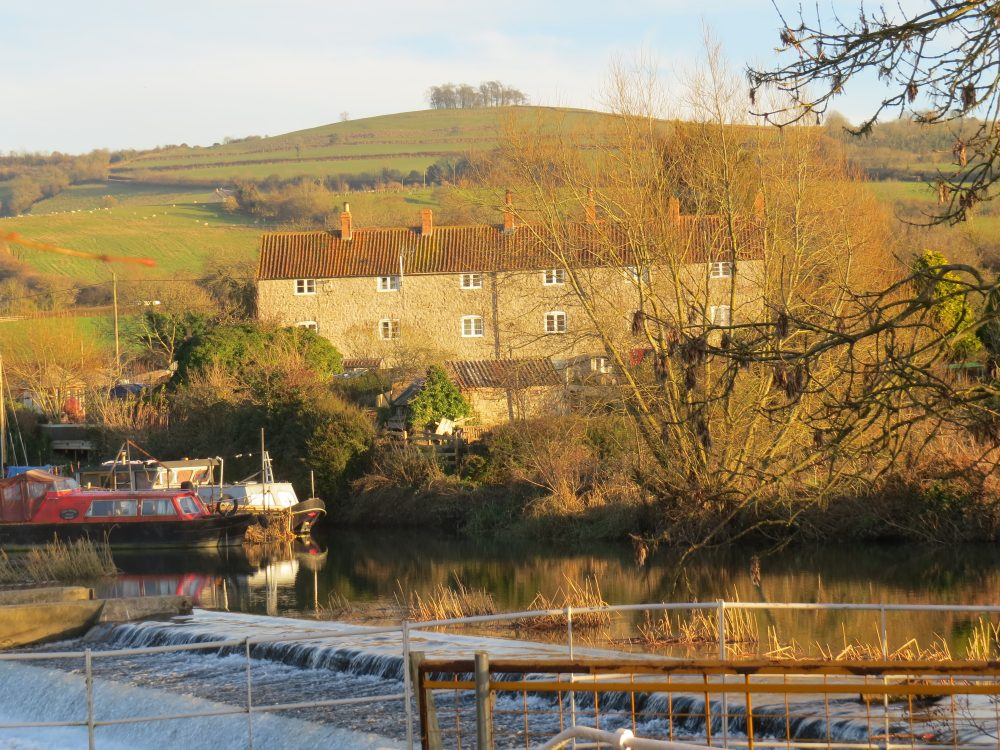 Kelston MIlls, the River Avon - and Kelston Round Hill – an ornamentally planted 'eye catcher' for Brown's Kelston Park. The 18th century ride from Kelston Park House to the Round Hill was to view the magnificent sweep of the River Avon, and the distant Welsh Hills.